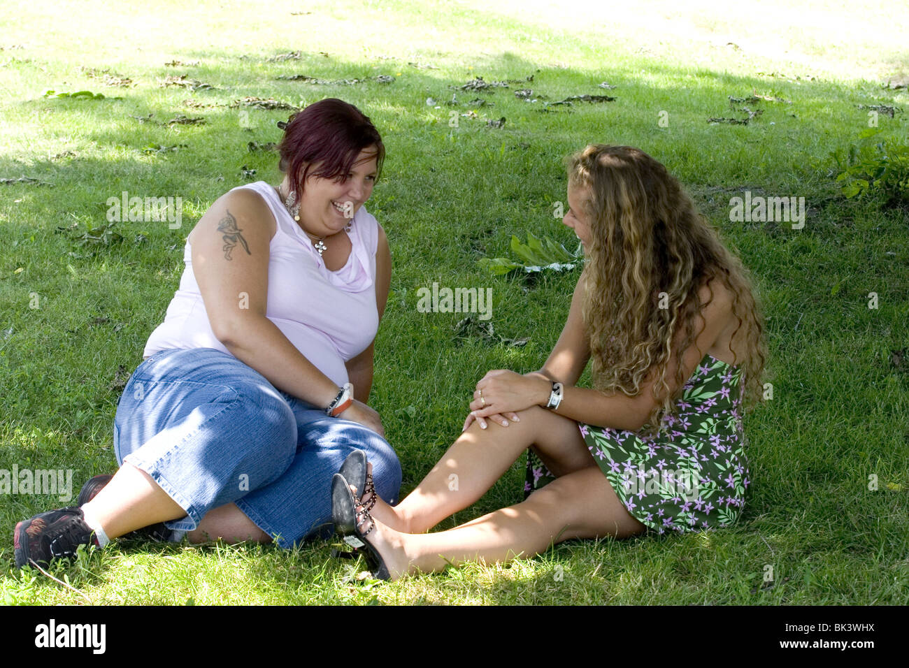 Slim and obese young women chatting in park, Shootcvs617001 - Stock Image