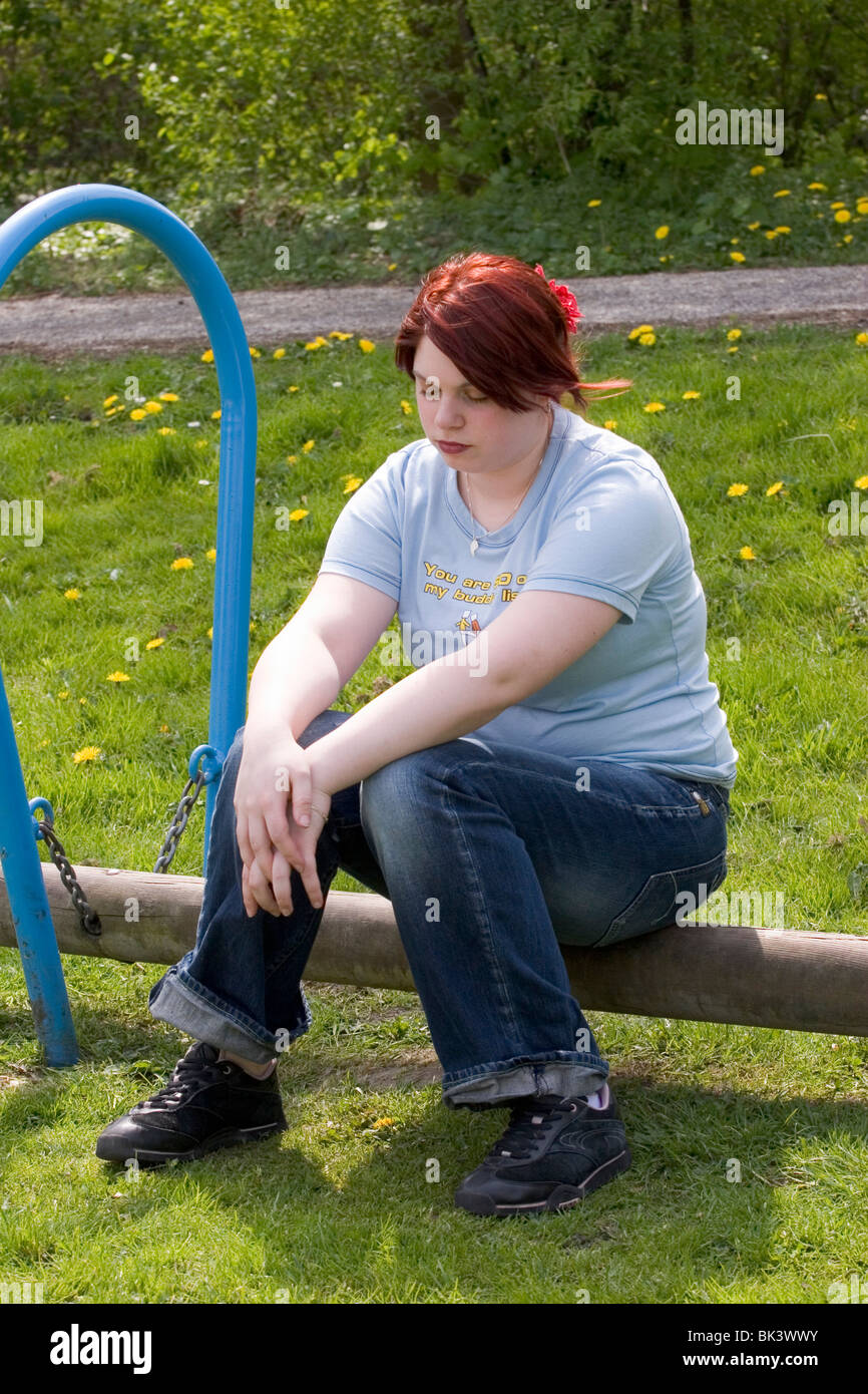 Plus sized young woman sit in park, thinking, looking down, sad and lonely. - Stock Image