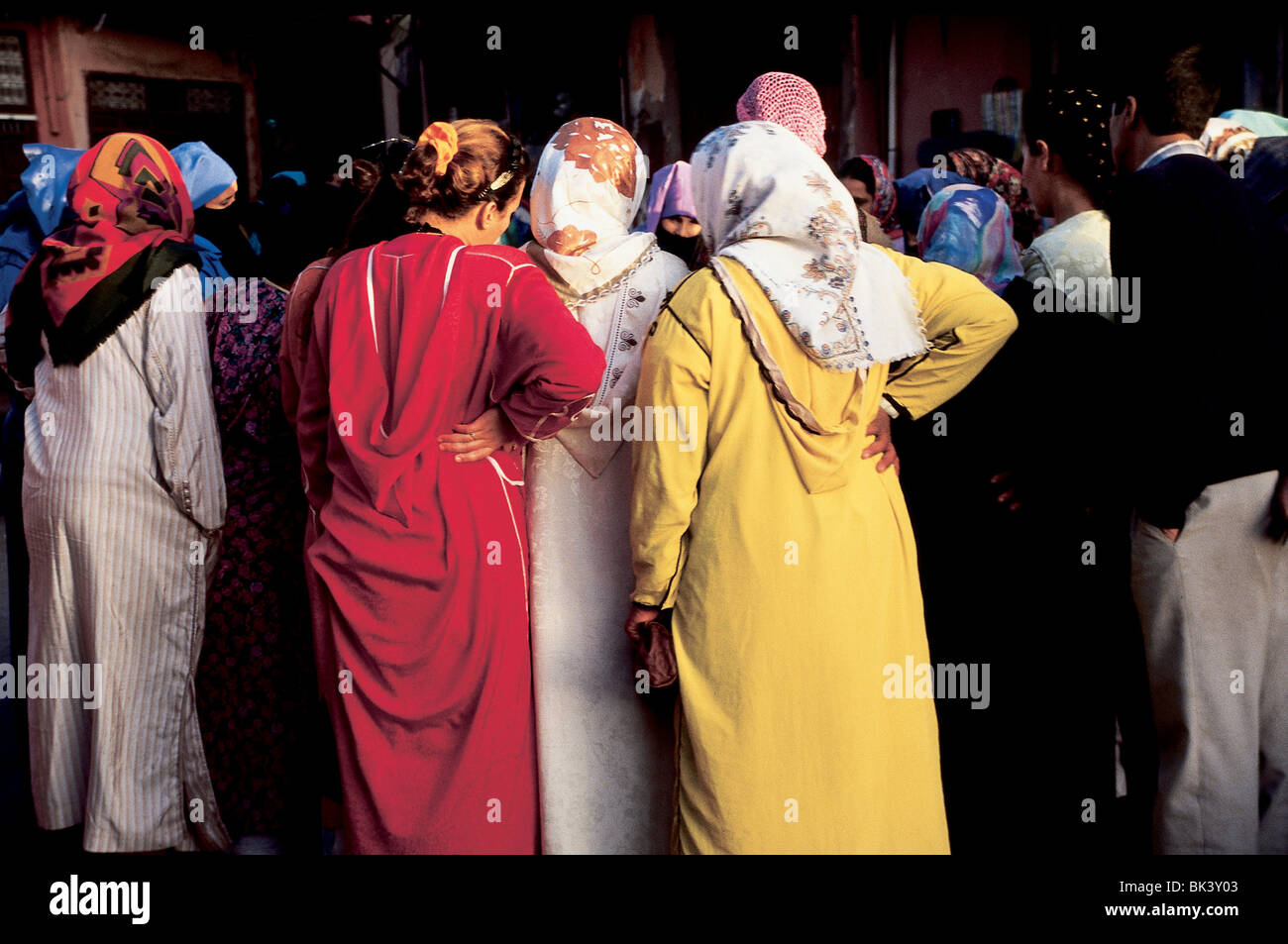 Women wearing brightly colored djellabas and headscarves, Marrakesh, Morocco - Stock Image