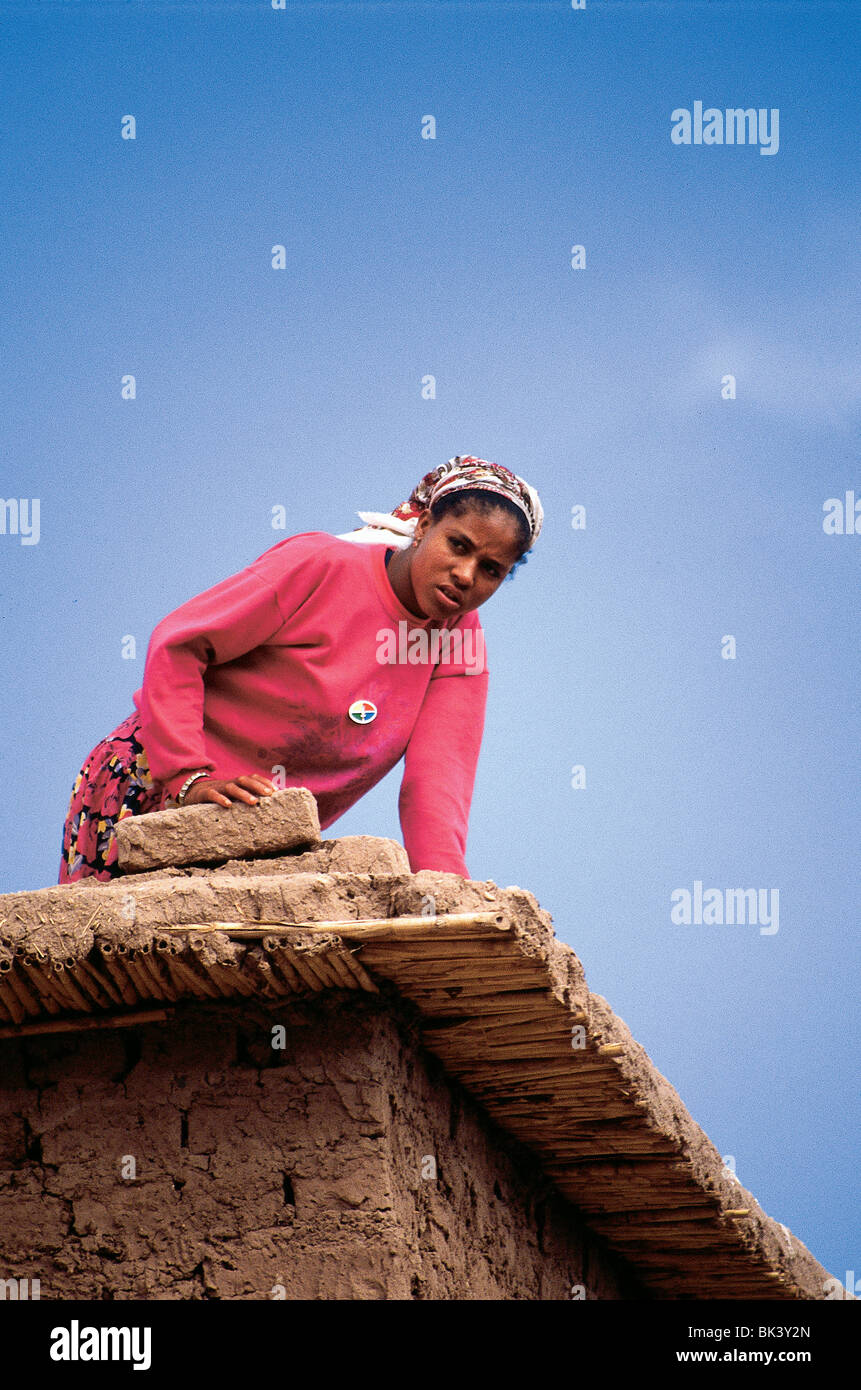 Young woman working on the roof of an earthen brick house in Ouarzazate Province, Morocco - Stock Image