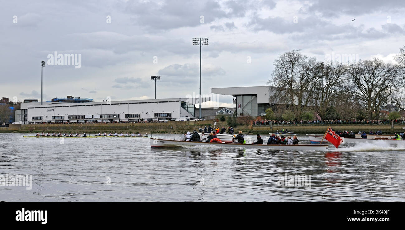 Oxford and Cambridge Boat Crews Racing past Fulham Football Ground - Stock Image