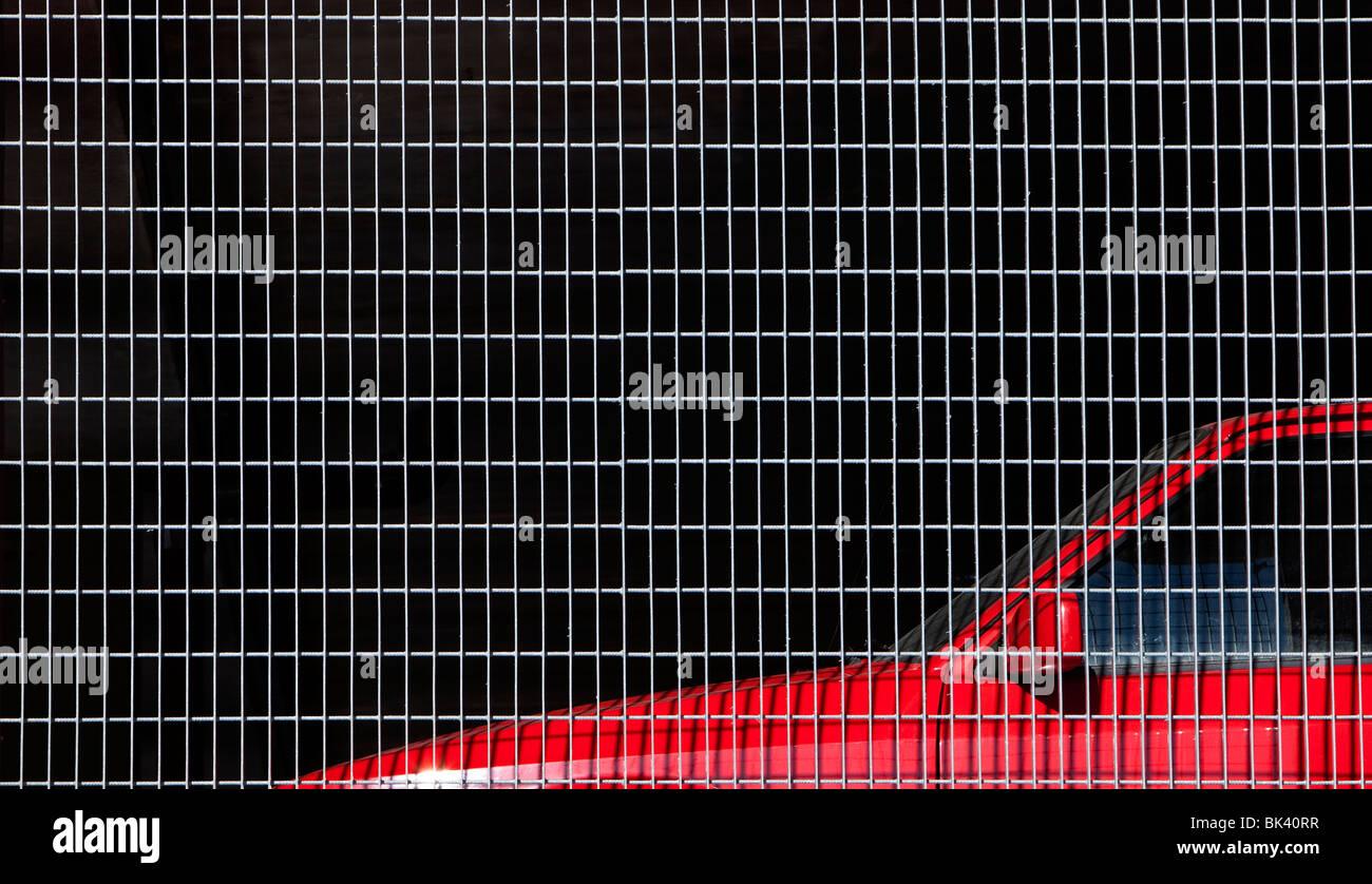 Red car behind metal mesh - Stock Image