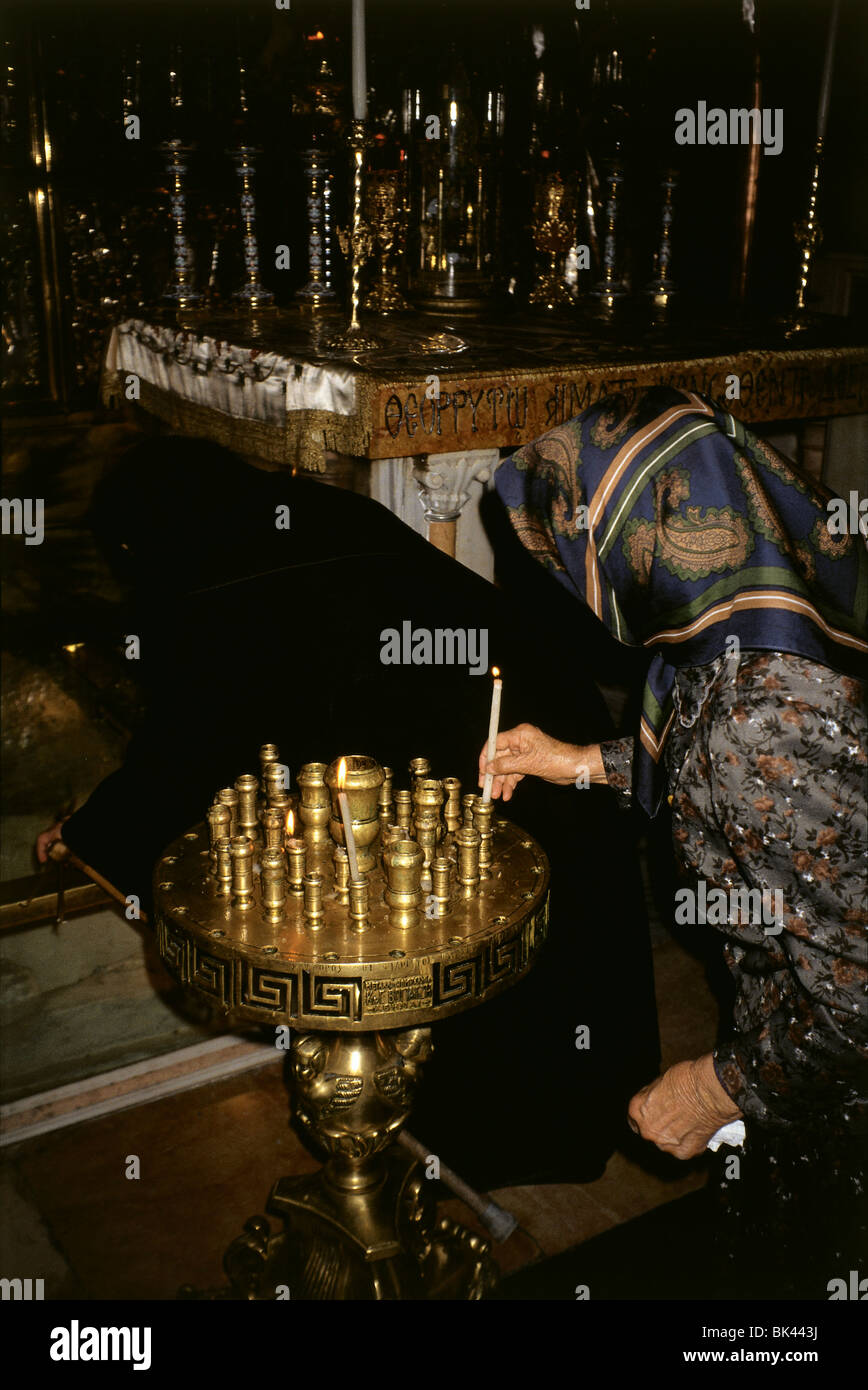 Woman lighting a candle in the Church of the Holy Sepulcher, Jerusalem - Stock Image