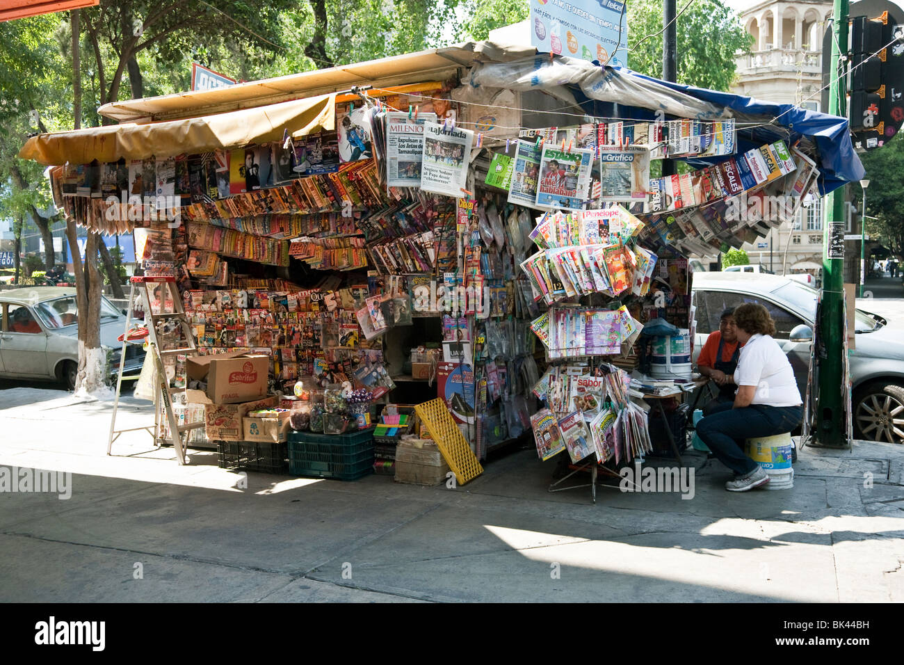cheerfully overloaded news stand with happy proprietor socializing on a beautiful day in the Roma district of Mexico - Stock Image