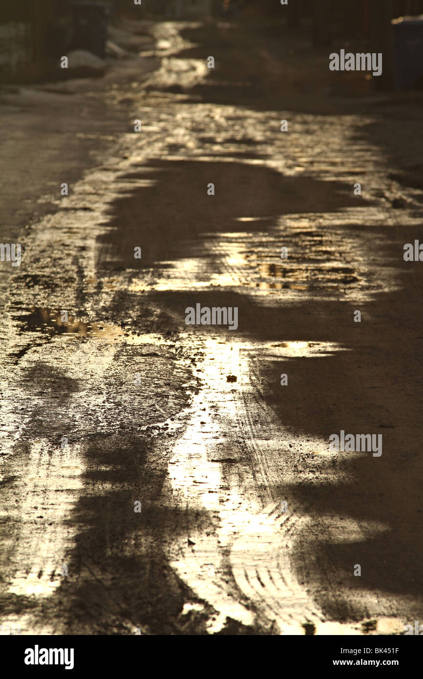 Tire tracks in a muddy city alley. - Stock Image