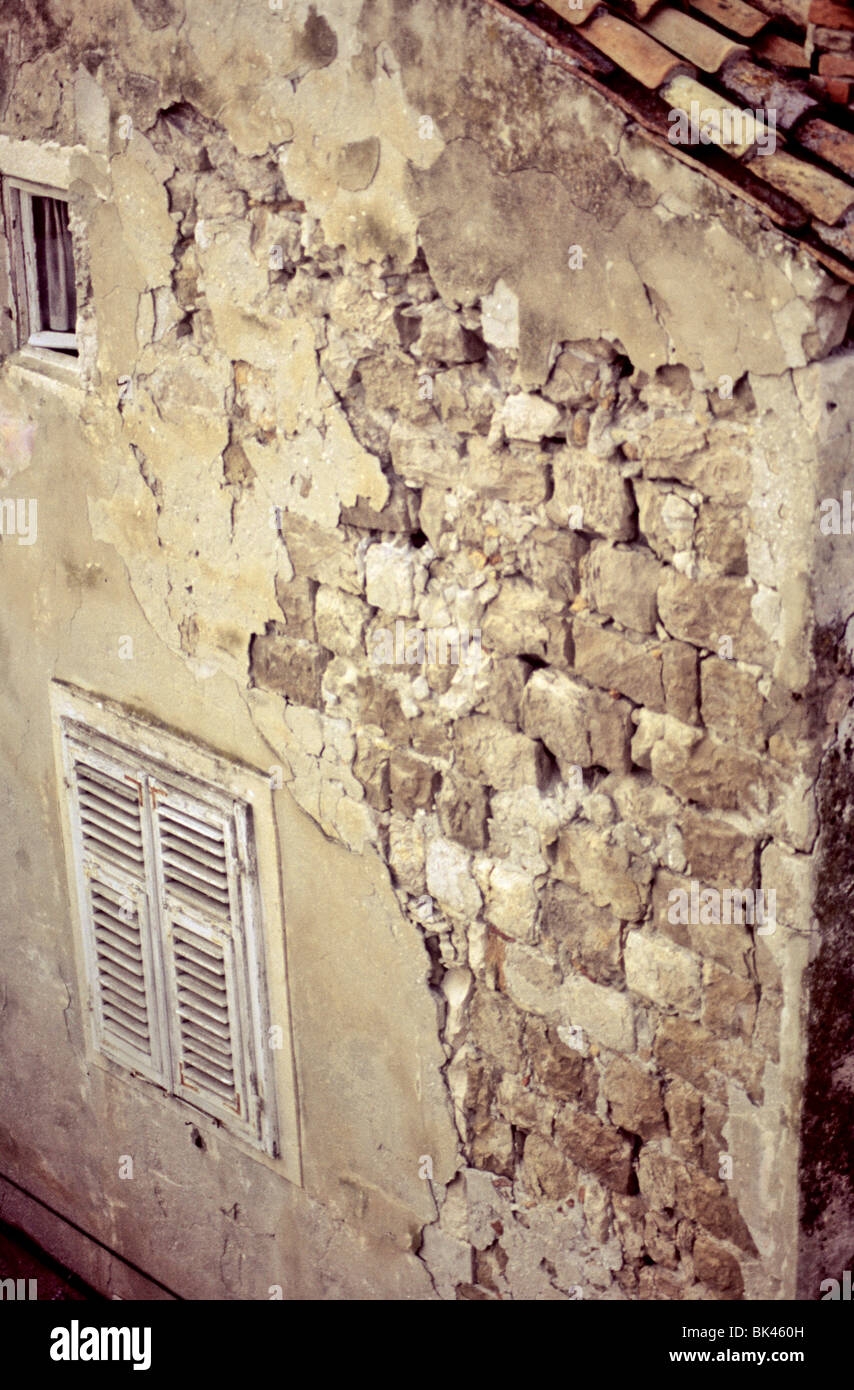 Decayed plaster and exposed stone walls of a multistory dwelling in Croatia - Stock Image