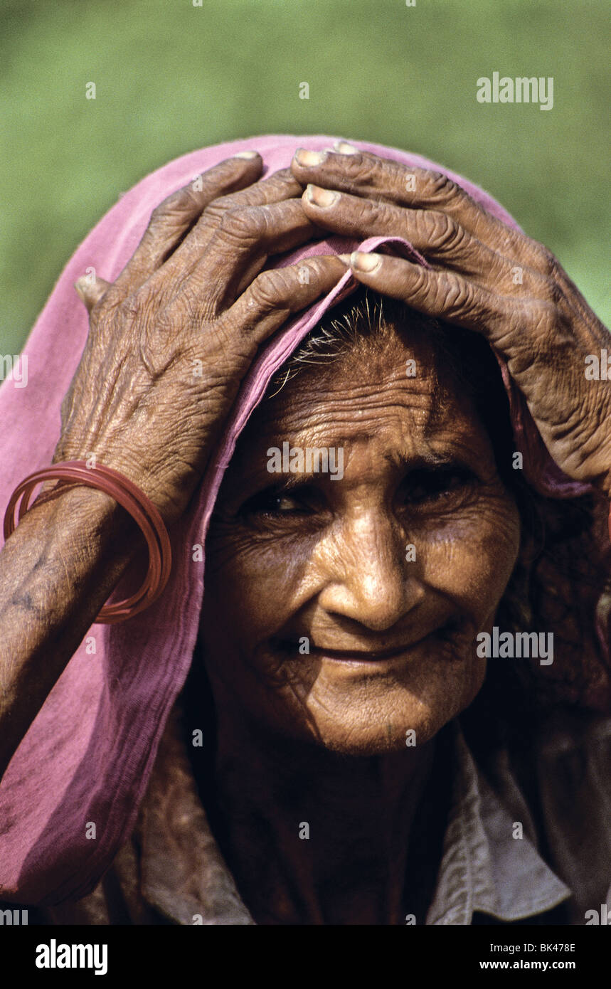Portrait of an elderly Indian woman with her hands on her head, India - Stock Image