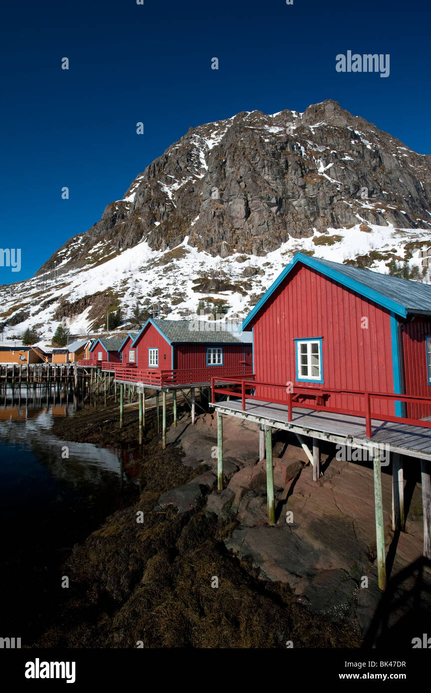 Traditional red wooden fishermen`s Rorbu huts by sea in Tind village in Lofoten Islands in Norway - Stock Image