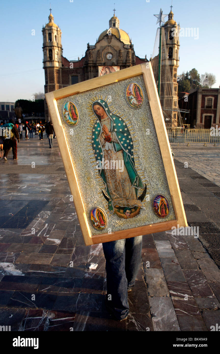 A pilgrim holds a image of the Virgin of Guadalupe on his shoulders in the Basilica of Guadalupe in Mexico City - Stock Image