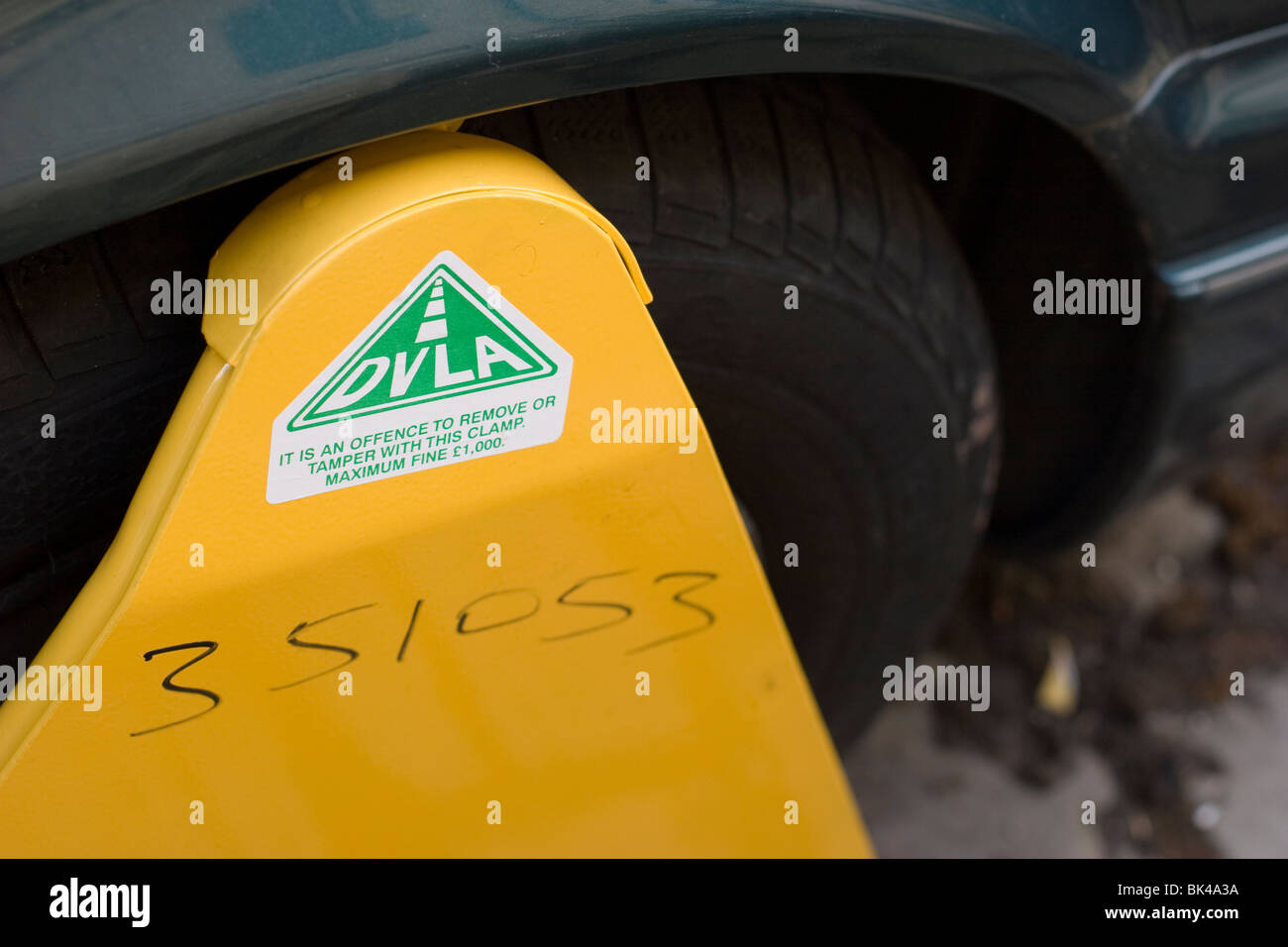 A DVLA clamp on a car wheel because the car had not been taxed. - Stock Image