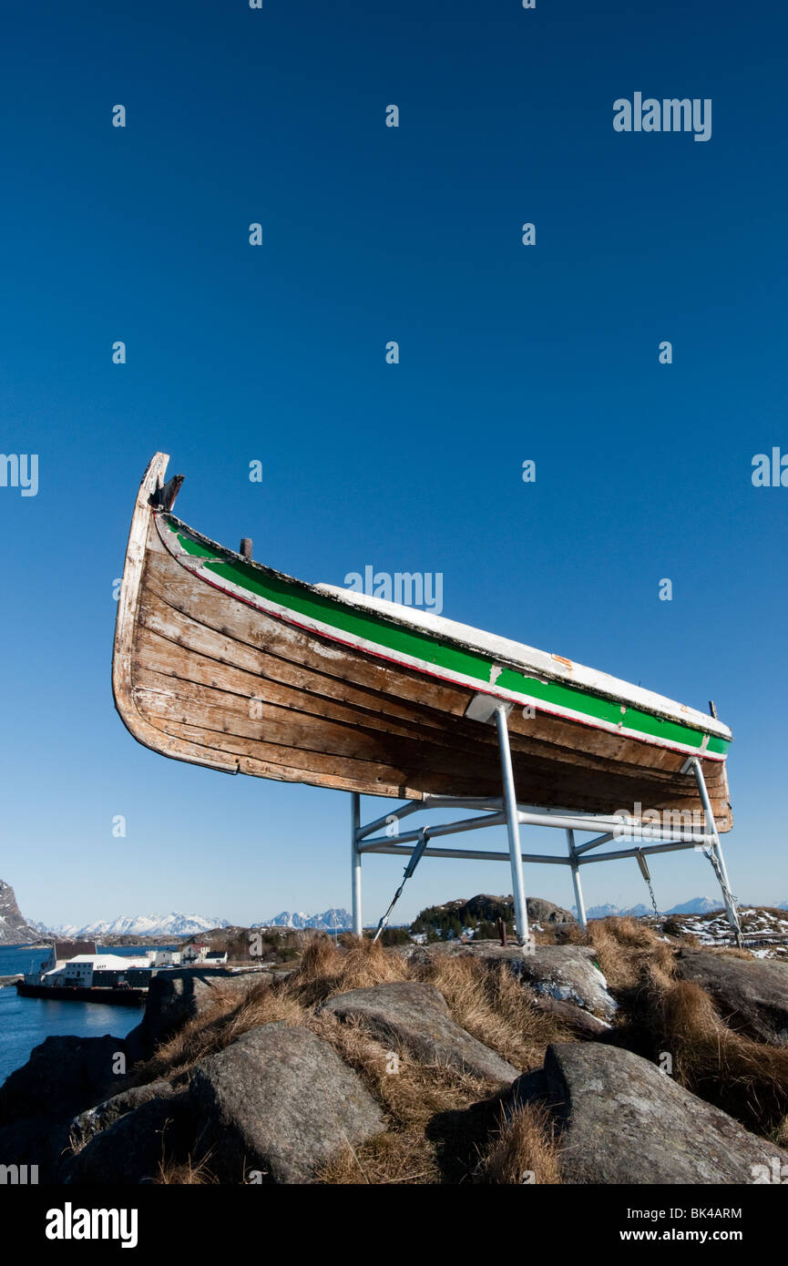 Old wooden fishing boat perched high above village of Henningsvaer in Lofoten Islands in Norway - Stock Image
