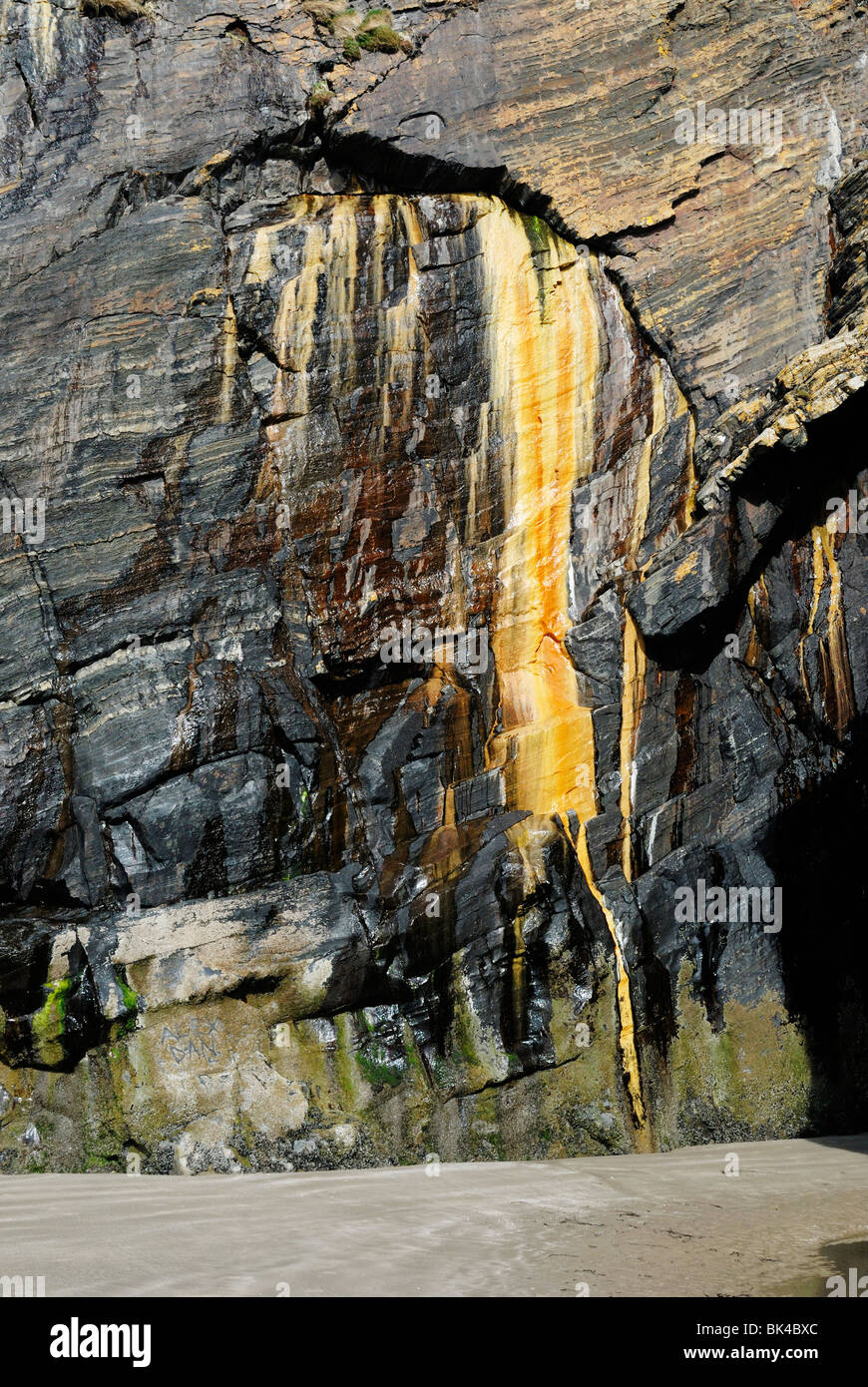 Mineral staining on a rockface on a sea cliff. - Stock Image