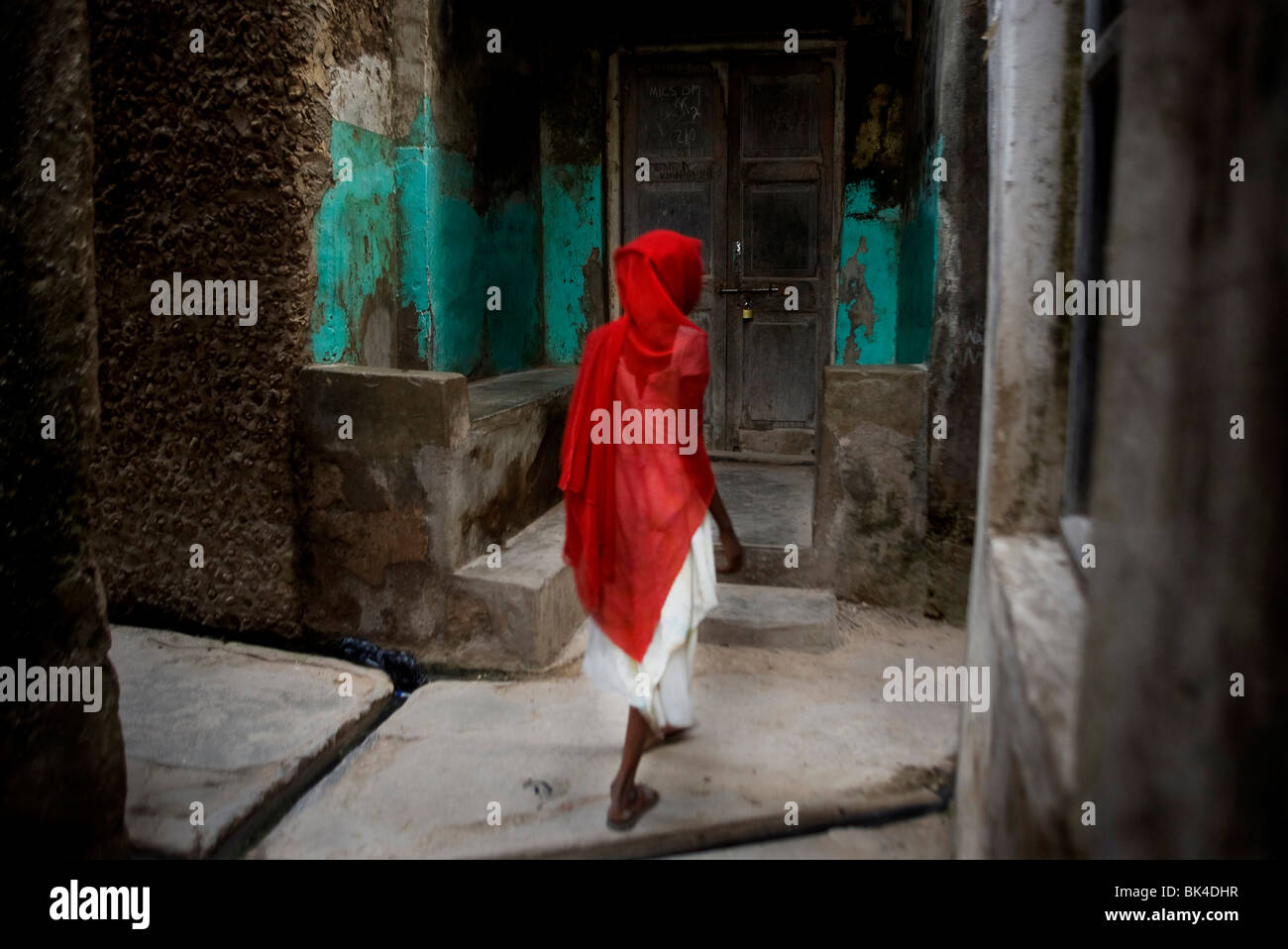 A woman wearing a red veil walks past Swahili houses in the town of Lamu island on August 18, 2009, Kenya. - Stock Image