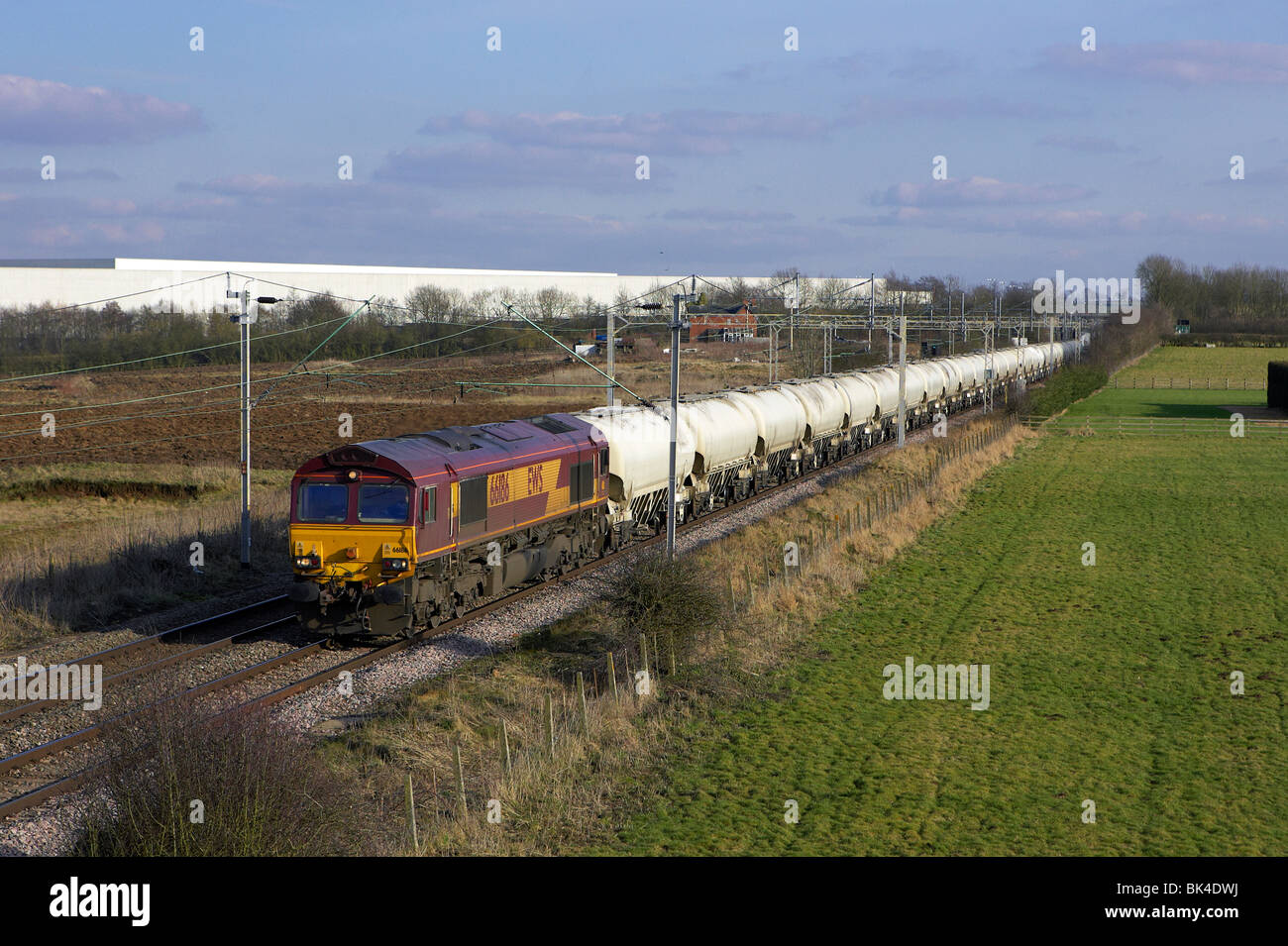 DBS 66186 heads north through Barby Nortoft with 6H50 12:58 Willesden-Tunstead cement on 02/03/2010. - Stock Image