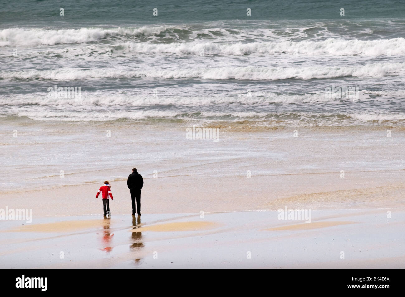 A father and daughter walking along Fistral Beach in Nerwquay in Cornwall.  Photo by Gordon Scammell - Stock Image