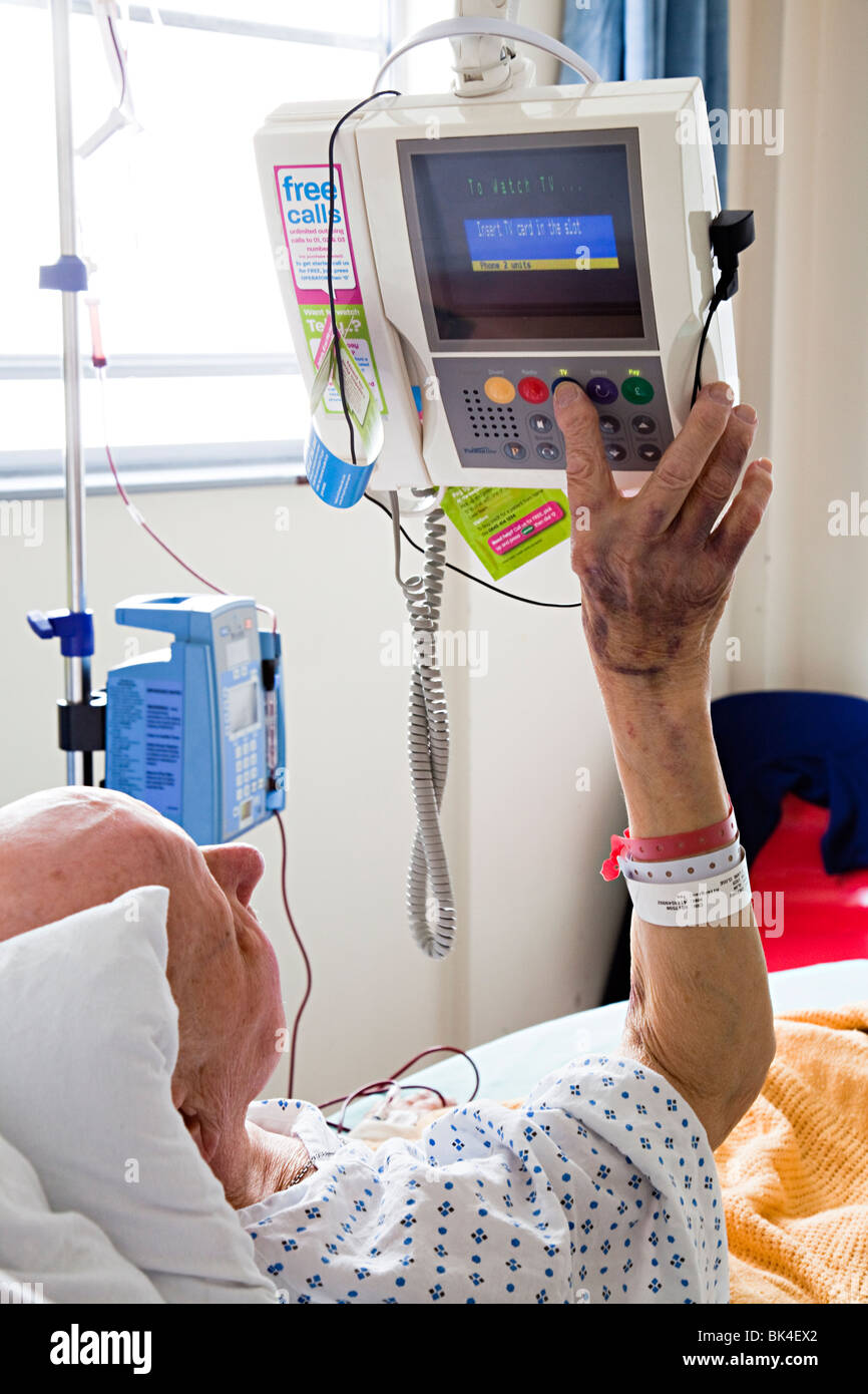 Patient in hospital bed adjusting television settings Wales UK - Stock Image