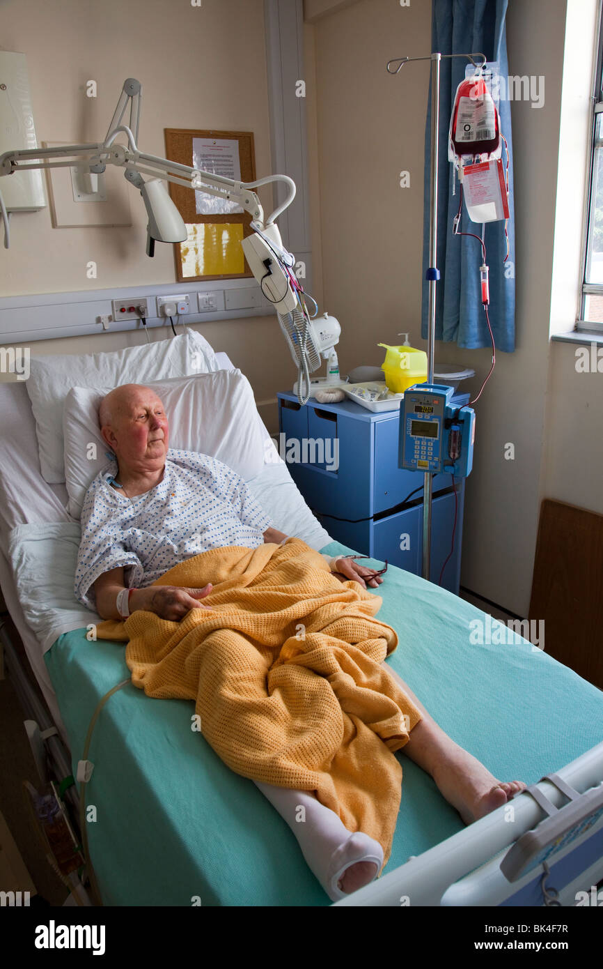 Patient in hospital bed undergoing blood transfusion Wales UK Stock Photo