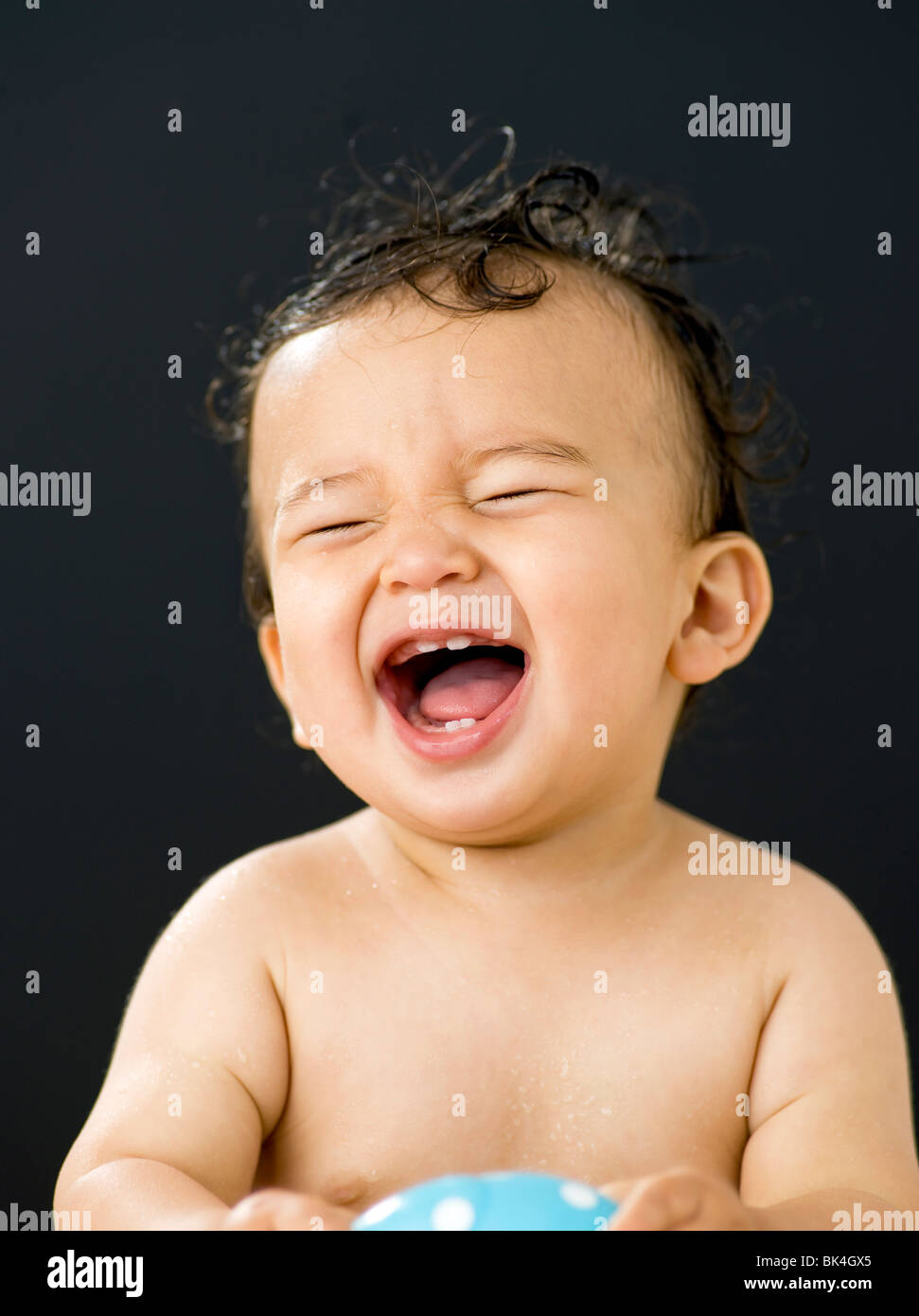 Happy baby in front of black background - Stock Image