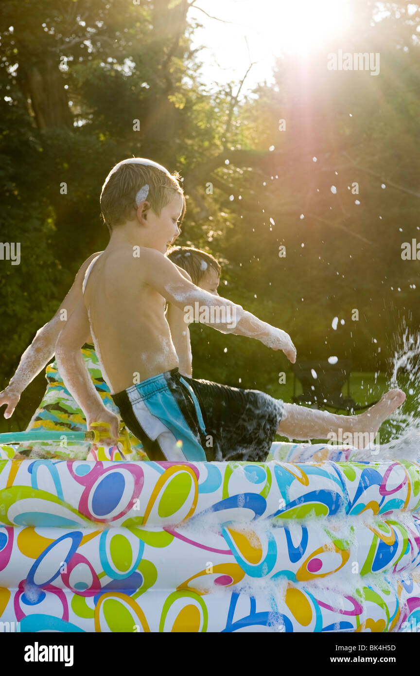 Boys playing in pool full of bubbles - Stock Image