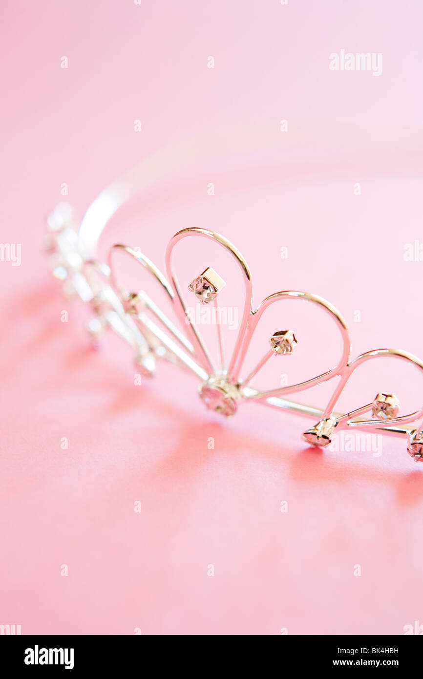 silver princess tiara often worn at weddings with jewels shot on pink background - Stock Image