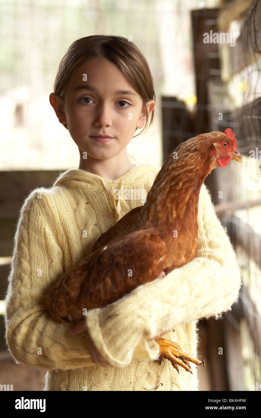 Girl with a big chicken in the chicken coup - Stock Image