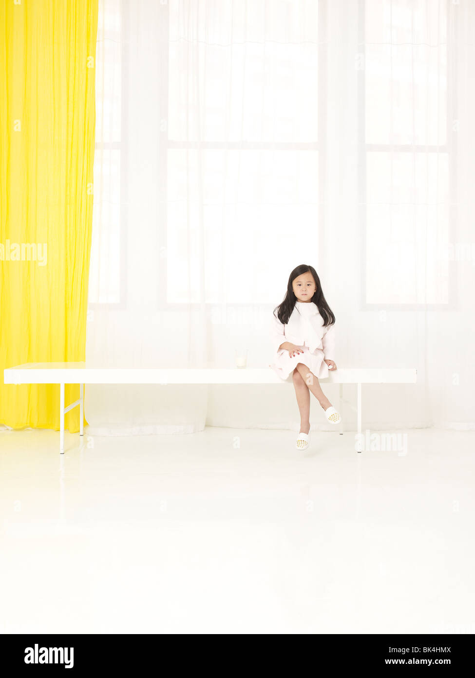 Girl in white sitting in white room Stock Photo