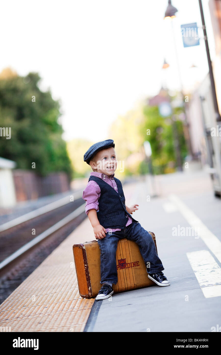 Young traveller sitting on suitcase - Stock Image