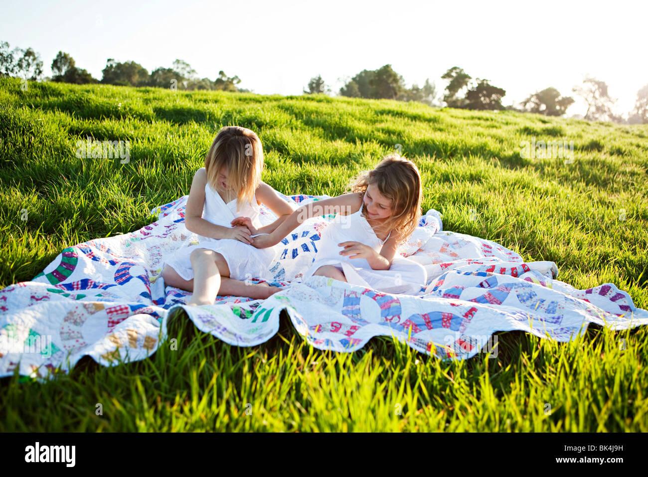 Girls on picnic blanket tickling each other - Stock Image