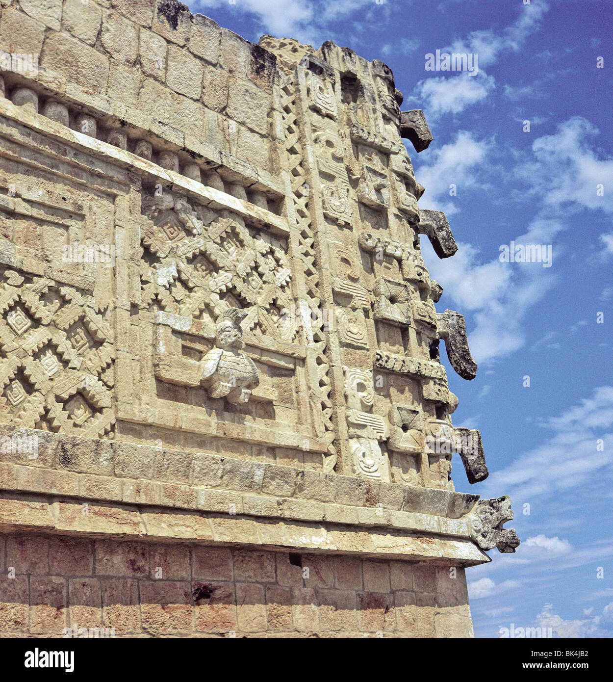 Architecture detail showing a relief sculpture of a human headed bird & a mask column at Nunnery Quadrangle in Uxmal Stock Photo