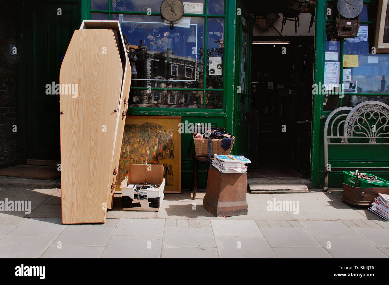 unused coffin standing outside antique junk shop - Stock Image