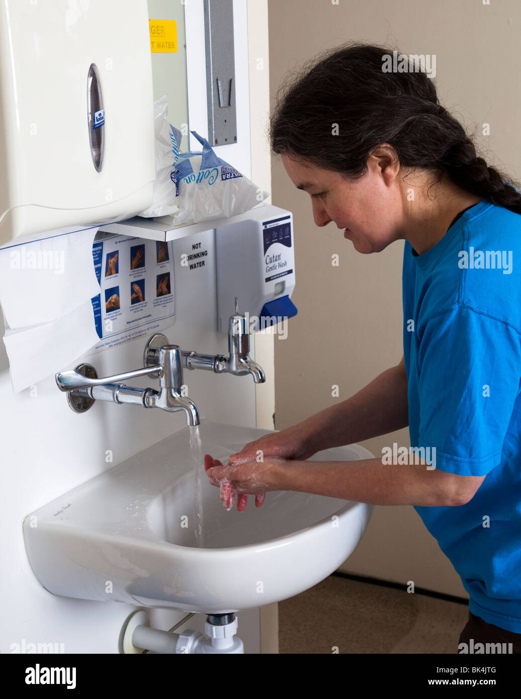 Woman washing hands in hospital sink Wales UK - Stock Image