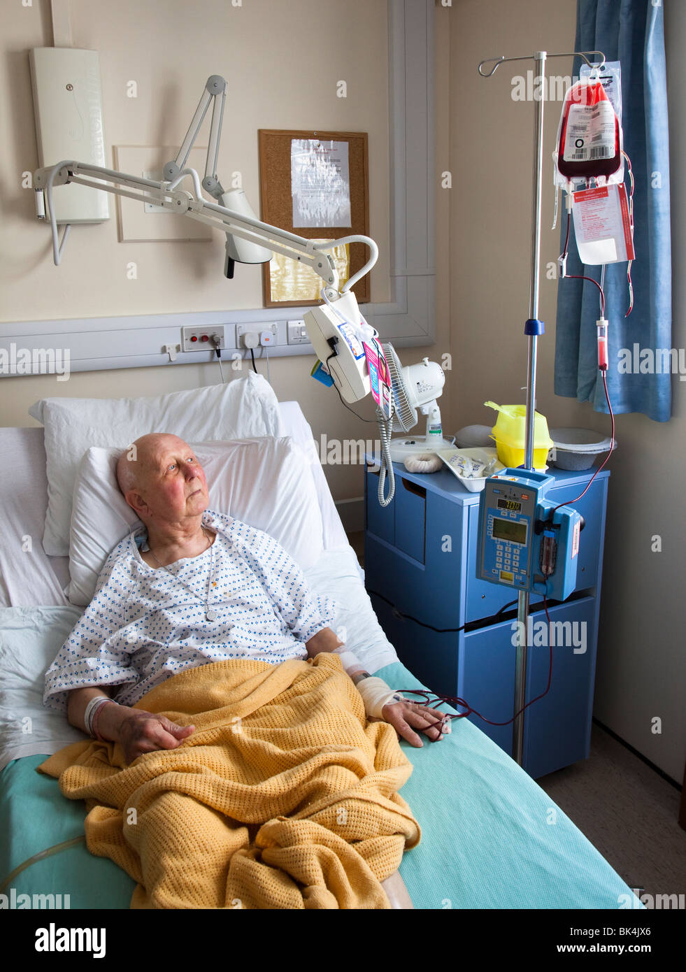 Patient in hospital bed watching television on swing arm while undergoing blood transfusion Wales UK - Stock Image