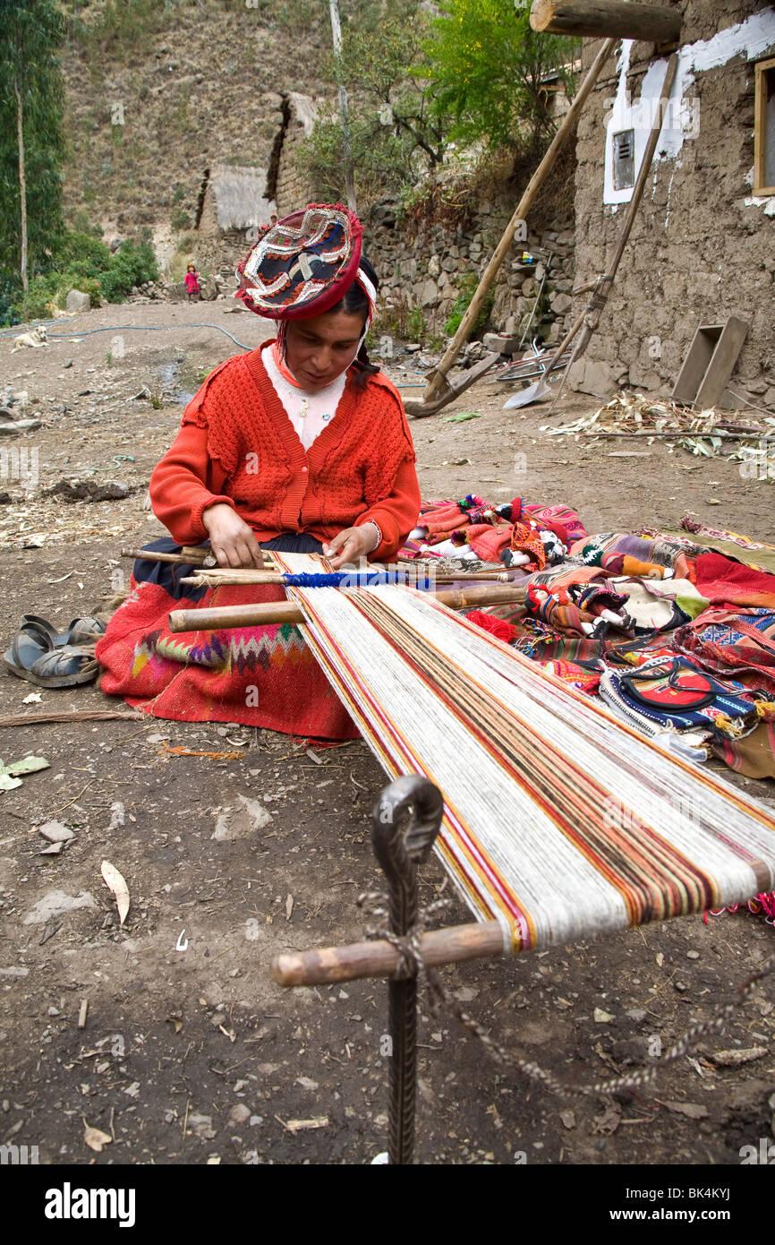 A Peruvian woman weaves wool using traditional natural tools. Patacancha Valley, Peru. - Stock Image