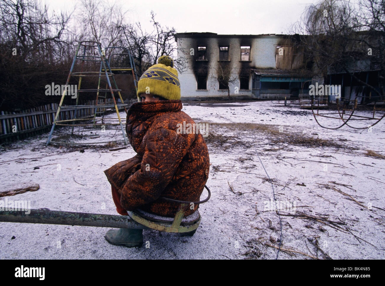 First Chechen War, 8 year old, Olla, sitting in the playground of her bombed out school South of Grozny in Chechnya. - Stock Image