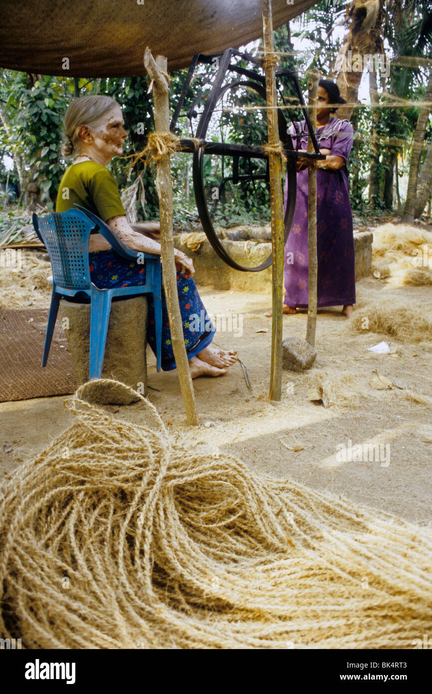 Woman making rope with coco fiber called 'coir' in traditional way in a backwaters village - Stock Image