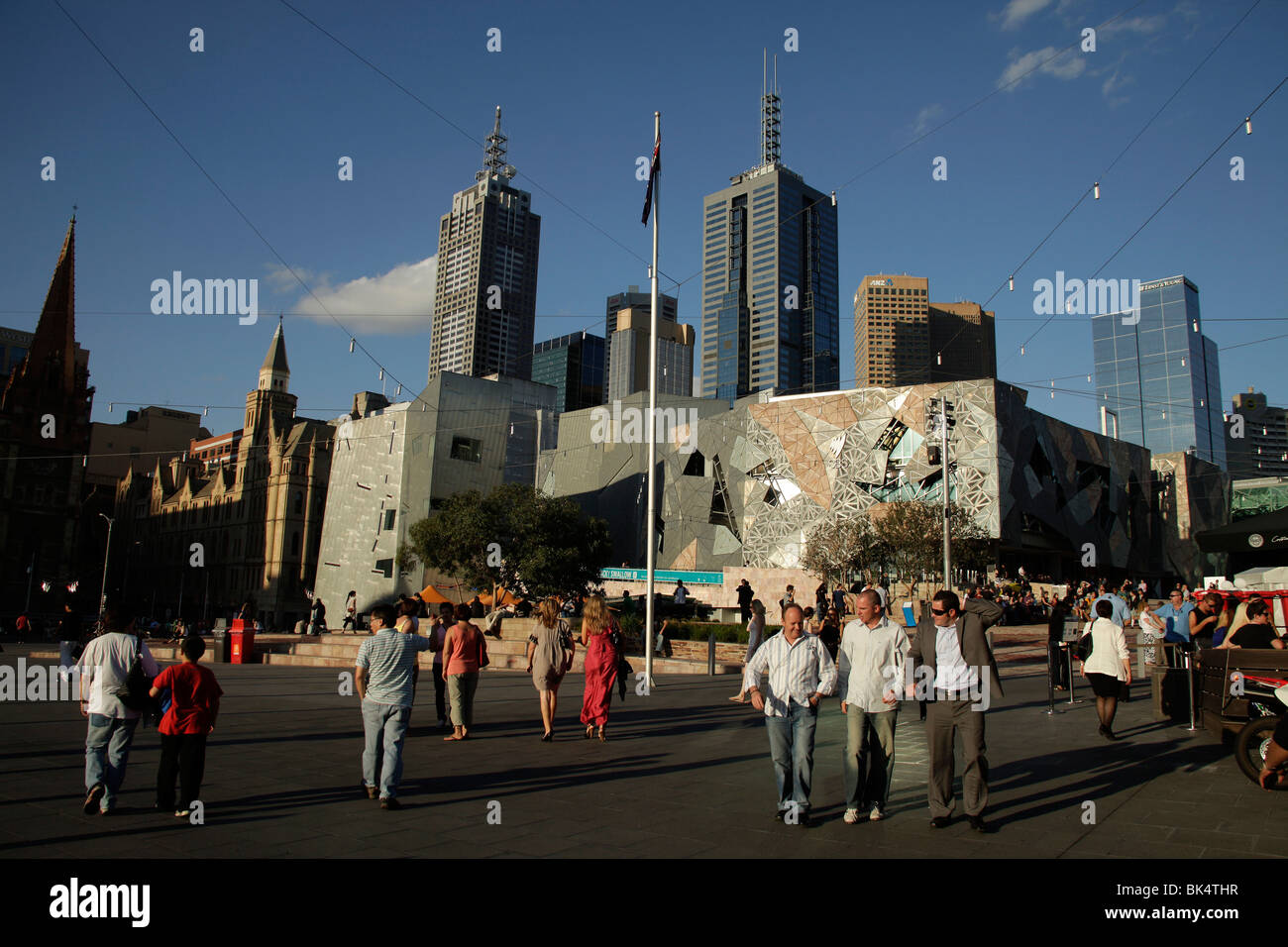 busy Federation Square and the Melbourne Skyline, Victoria, Australia - Stock Image