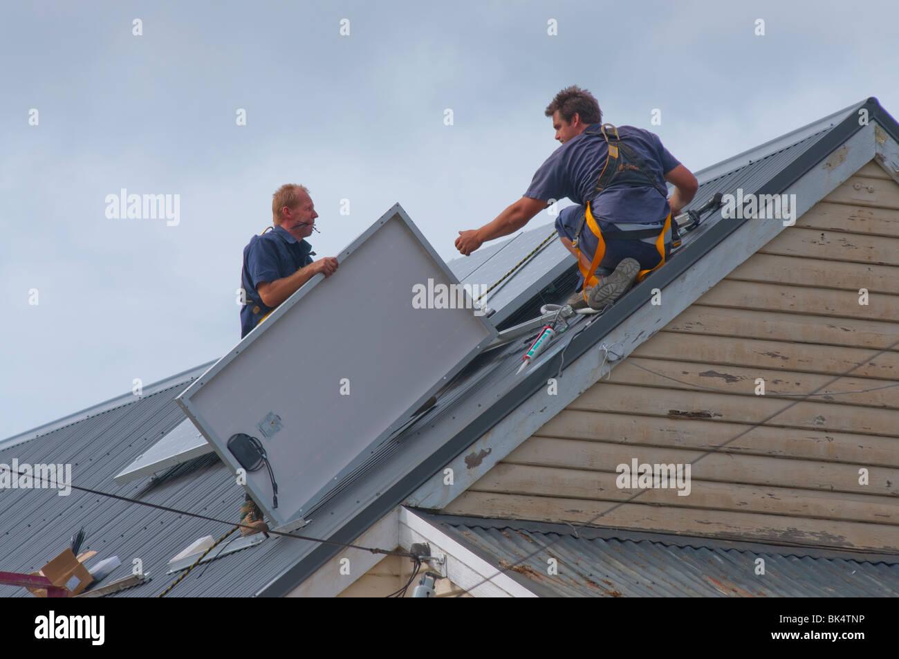 Workmen installing solar panels on roof in Hobart Tasmania Australia - Stock Image