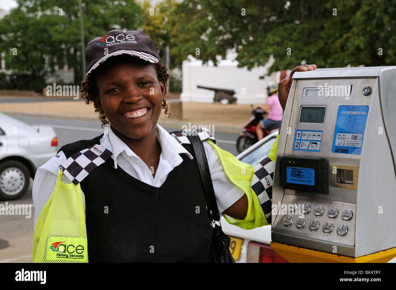 portrait of a smiling happy parking meter attendant with the payment machine in Stellenbosch town  western Cape - Stock Image