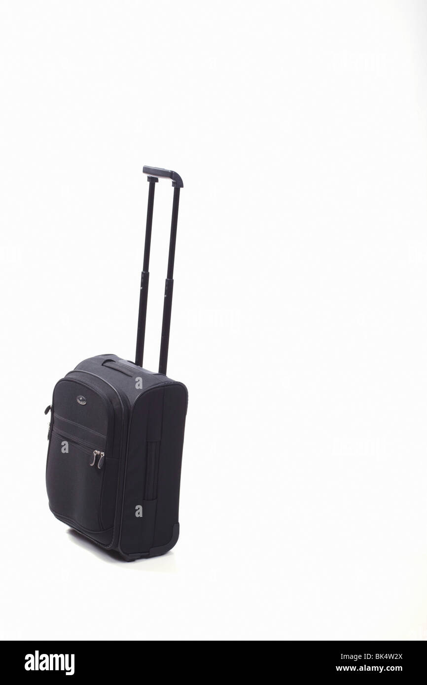 A black trolley case with handle extended. Isolated. Copy space. - Stock Image