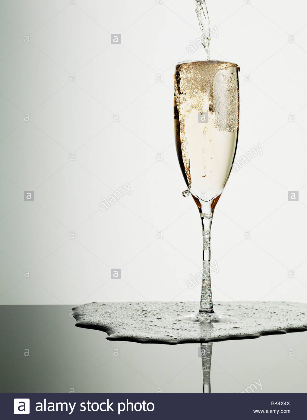 Champagne pouring into glass and overflowing - Stock Image