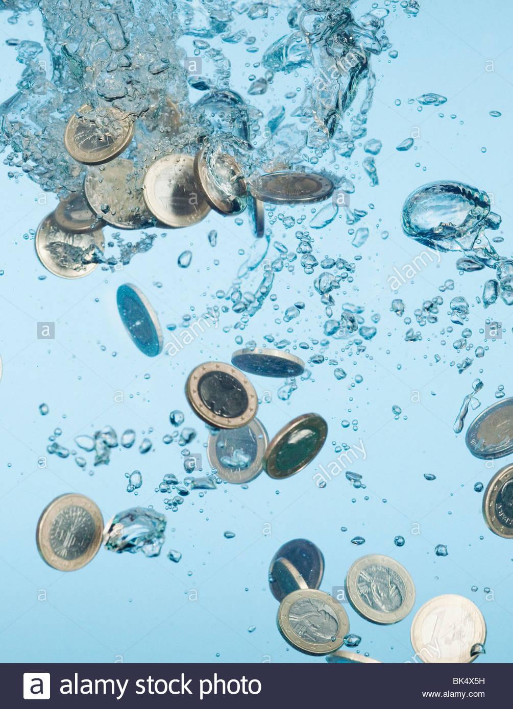 Close up of Euro coins splashing in water - Stock Image