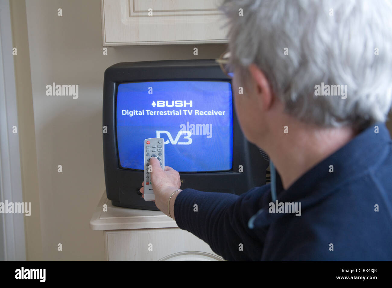 Close up Female senior citizen using a remote control for the Digital switchover on her portable Television set - Stock Image