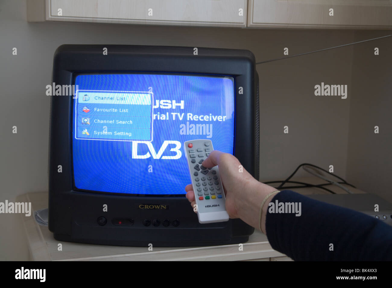 Close up Hand holding a remote control to start the Digital switchover on a portable Television set - Stock Image