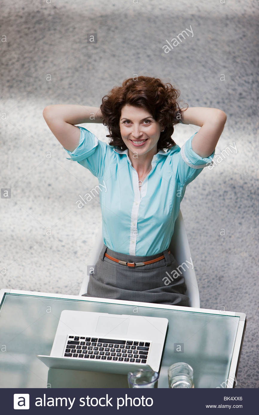 Businesswoman with laptop sitting with hands behind head - Stock Image
