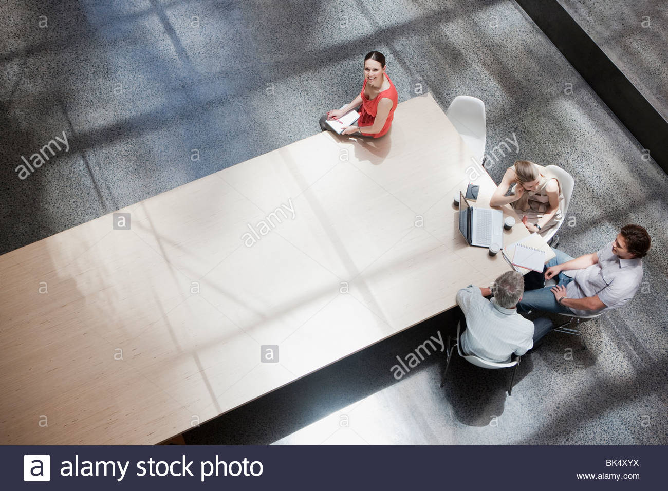 Businesswoman working apart from co-workers at conference table - Stock Image