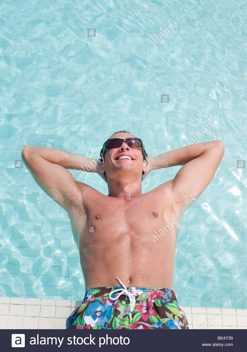 Man leaning back in swimming pool with hands behind head - Stock Image