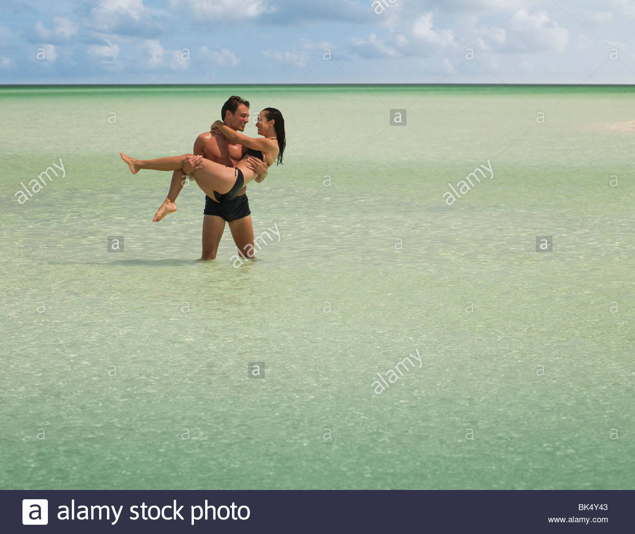 Man carrying woman and wading in ocean - Stock Image