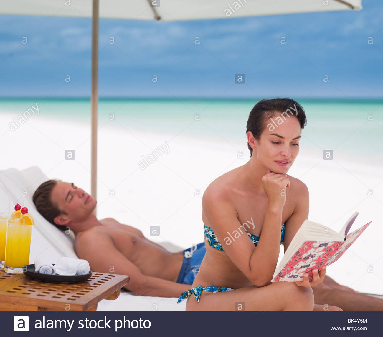 Woman reading book and man laying on lounge chair on beach - Stock Image