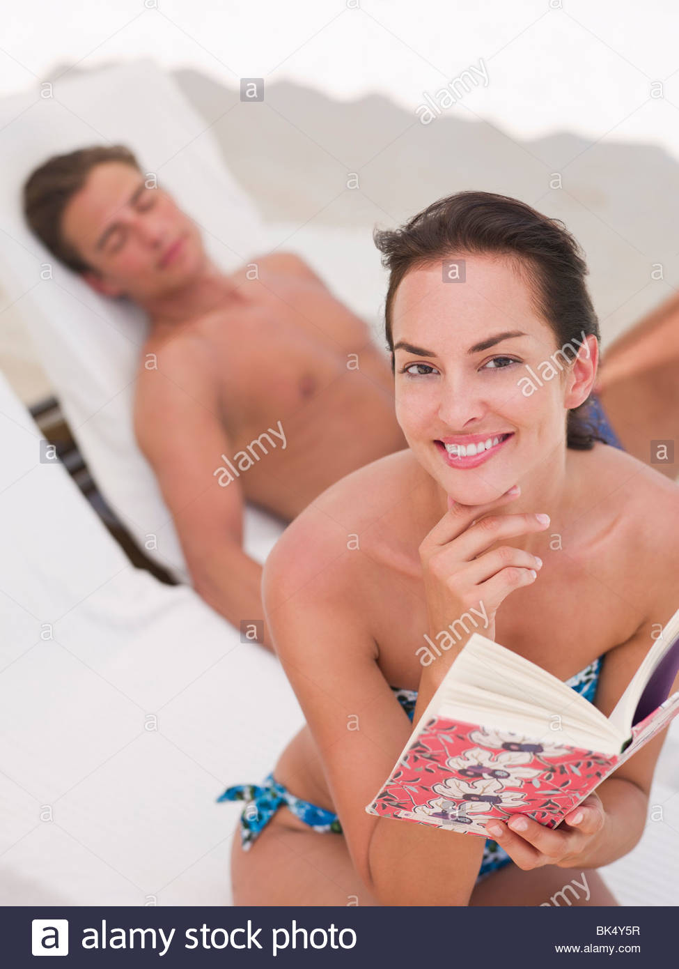 Woman reading book and man laying on lounge chair - Stock Image
