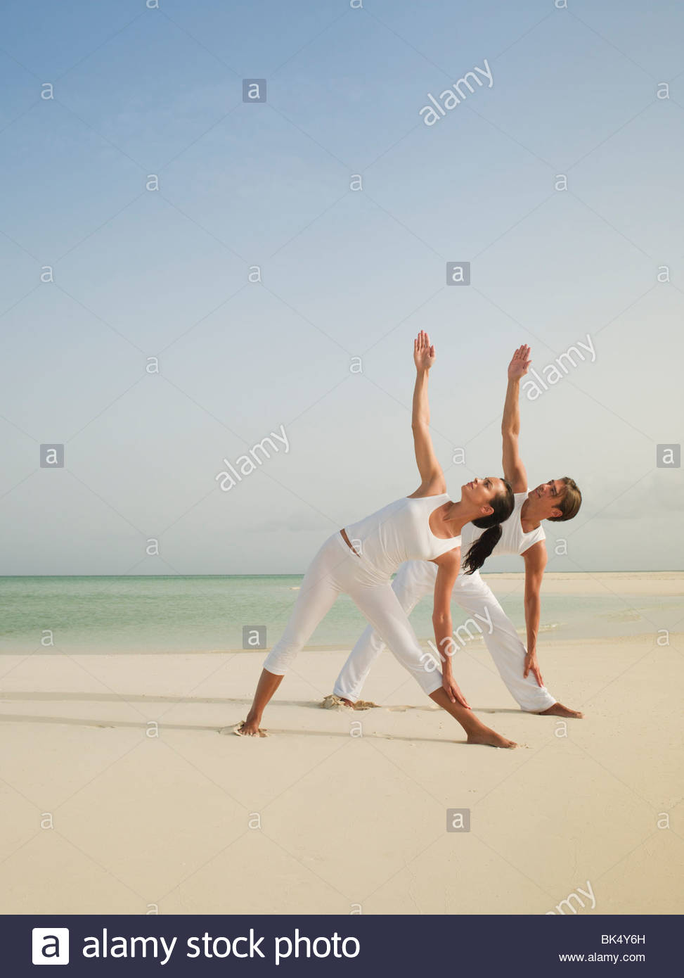 Couple In Triangle Yoga Pose On Beach